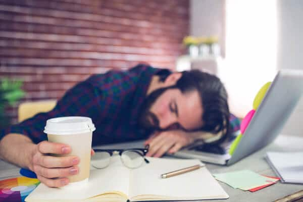 man tired working laptop coffee asleep workplace stress and wellbeing
