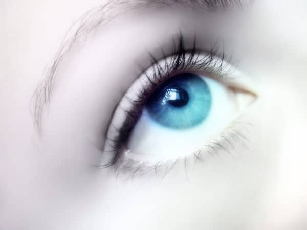 a female eye, looking up towards a focal point during an eye fixation hypnotic induction
