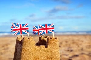A sandcastle at the beach with british flags on the turrets.