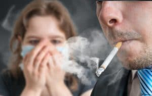 Man smoking cigarette with young girl in the background trying not to inhale passive smoke.