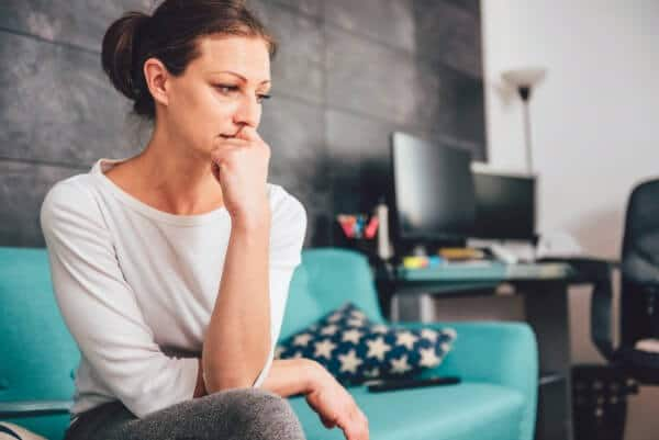 Woman on sofa engaging in negative mental rehearsal, looking really upset.