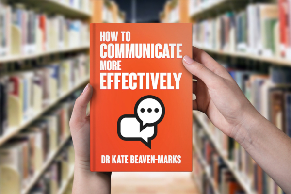 Person in library holding a copy of How to Communicate More Effectively by Dr Kate Beaven-Marks