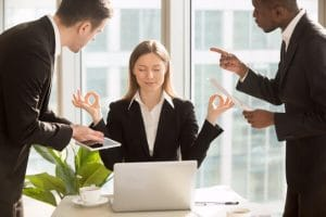 Woman using self-hypnosis at work to deal with stress, when colleagues are shouting at her.