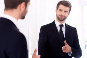 Therapist employing self care tips, using therapy on himself, looking in the mirror.