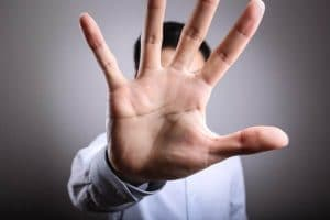 mans hand giving stop signal, to stop seeing clients if suffering coronavirus covid-19 symptoms