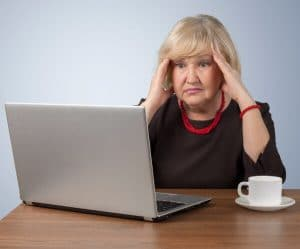 Hypnotherapist struggling with self-care, sat at laptop stressing about business admin.