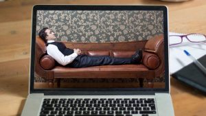 Man on a couch, on a laptop, during an online hypnotherapy session