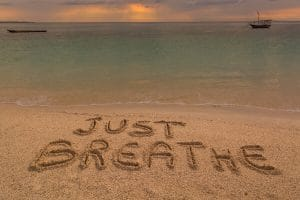 the words just breathe written in the sand on a beach