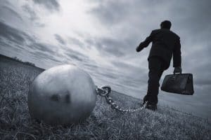 a therapist in a business suit with a ball and chain attached to his ankle