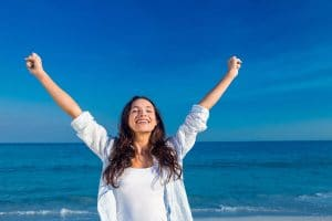Woman happy, arms in the air, at the beach, having solved her problems with hypnotherapy
