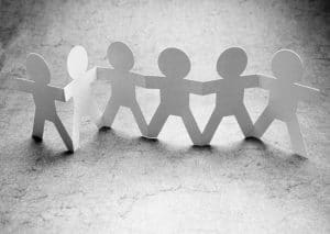 Image of paper people holding hands, for support.
