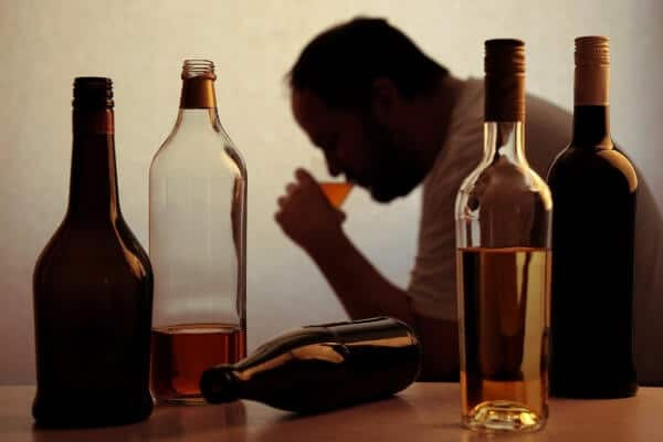 Silhouette of a man drinking alcohol due to social anxiety