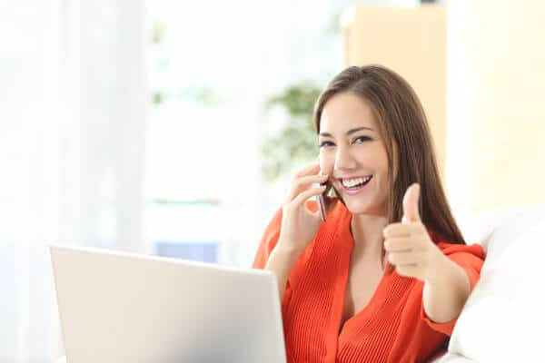 Hypnotherapist on the phone to a client, with her thumb up, smiling.