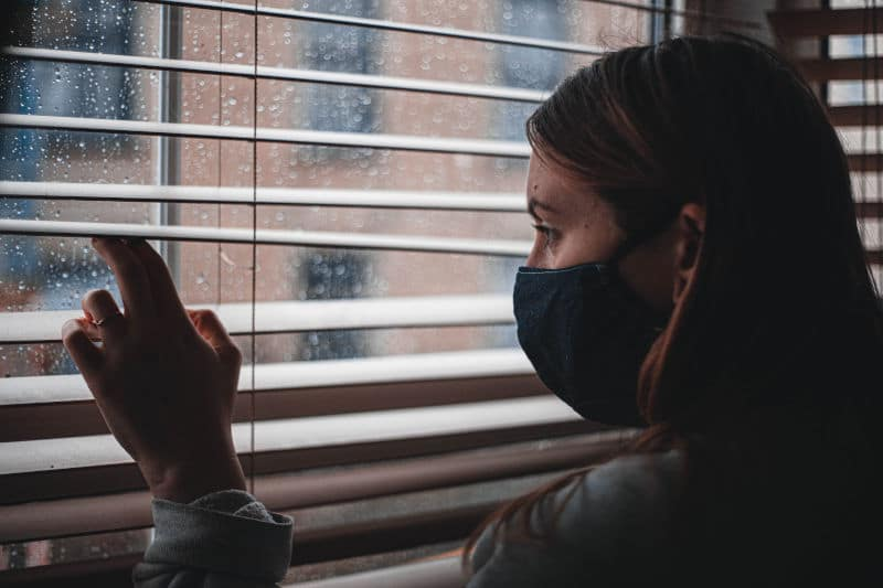 Woman in mask, in lockdown, staring sadly through a rainy window to the outside world