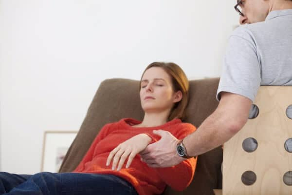 woman hypnotised by a rapid induction, the hypnotherapist holding her arm to test for depth